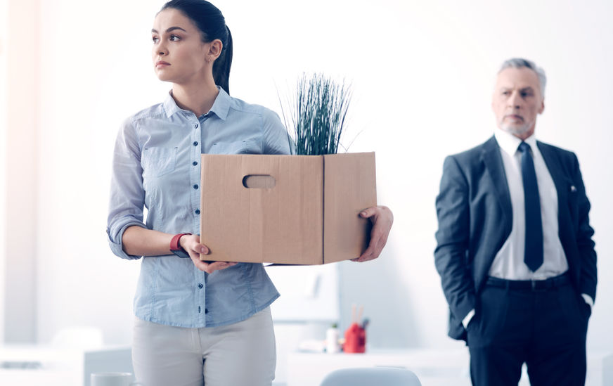 88846299 - fired young brunette with box full of stuff leaving office